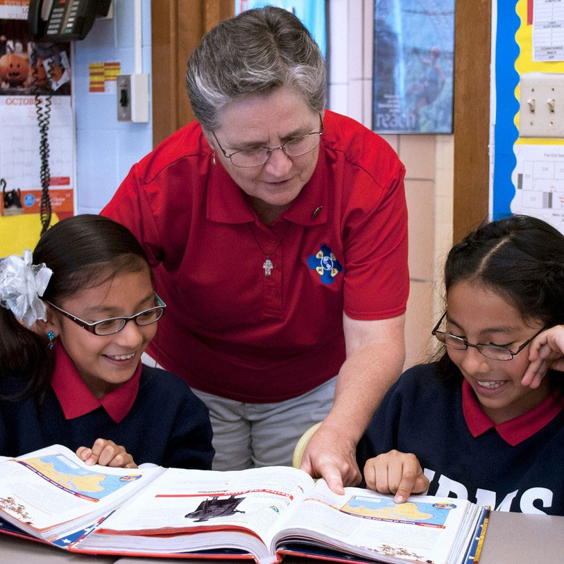 Sister Gladys Cortade works with two students at Notre Dame Middle School in Milwaukee.
