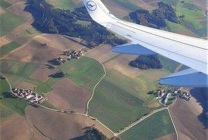 Blick über die Tragfläche eines Flugzeug über eine Landschaft